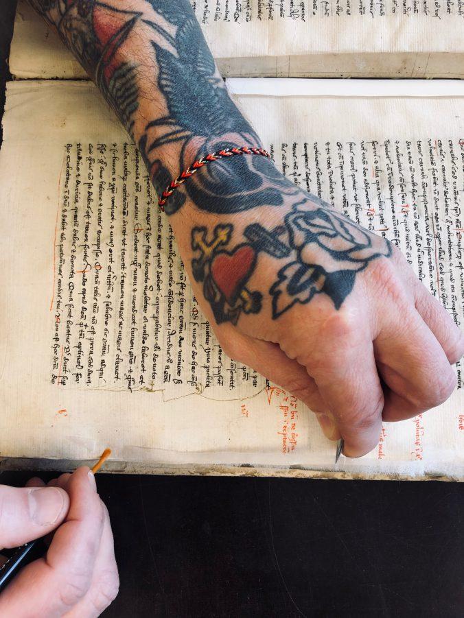 Bokbindare Adam jobbar med lagning av en handskrift. Bookbinder Adam working on a manuscript.