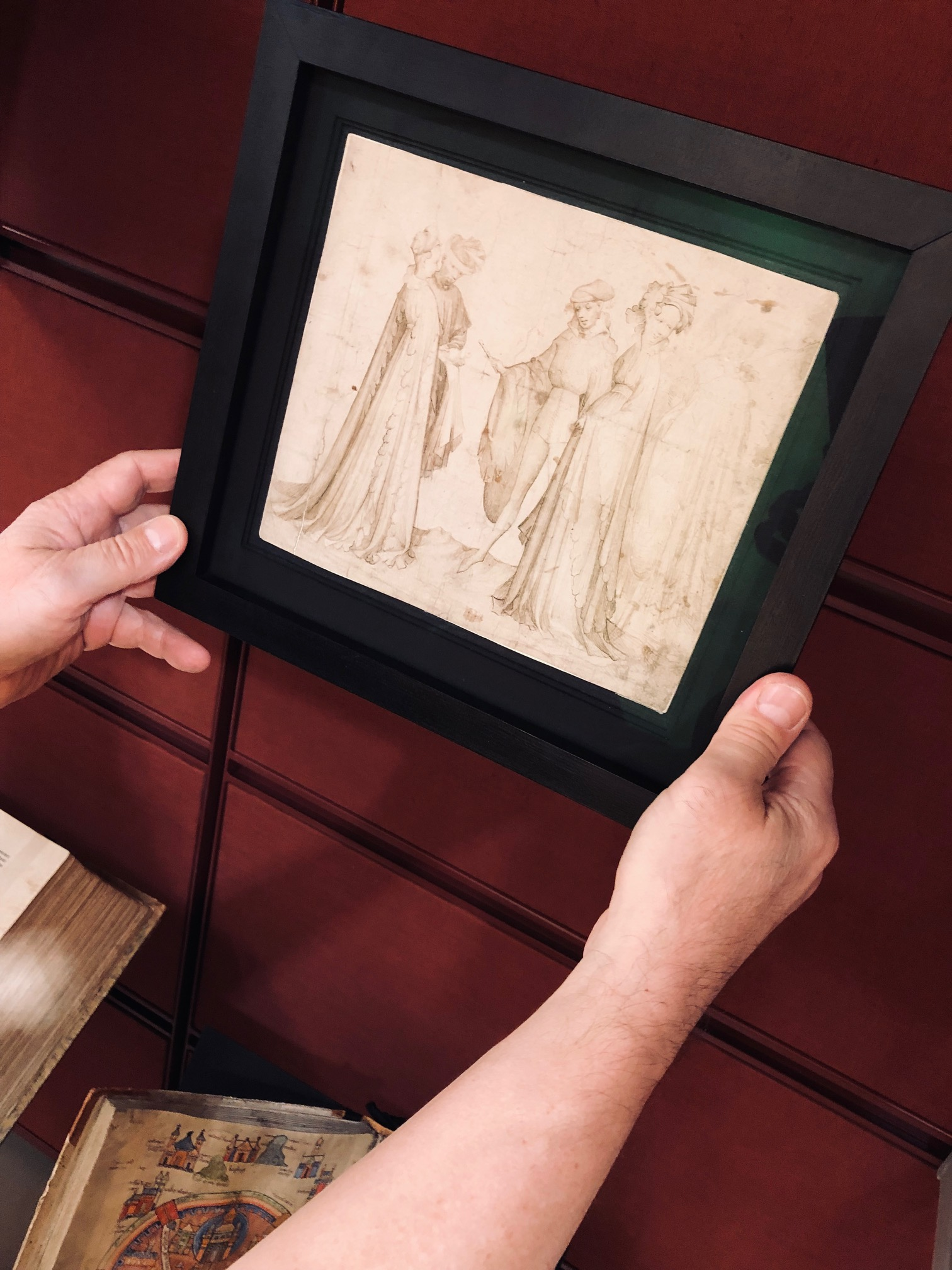 Två händer håller i tavla, Hovfolk från Geldern. Two hands holding framed drawing, Elegant Company in Courtly Dress from Guelders